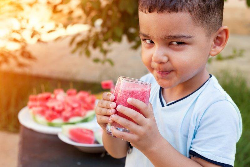 Child drinking watermelon juice in garden with watermelon nearby